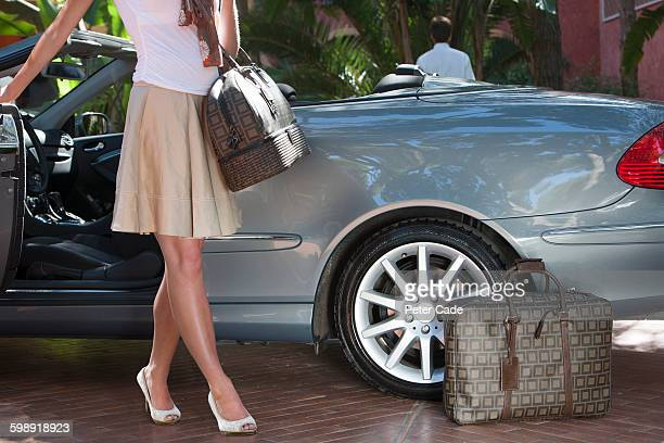 woman getting out of nice car with luggage - prestige car stock pictures, royalty-free photos & images