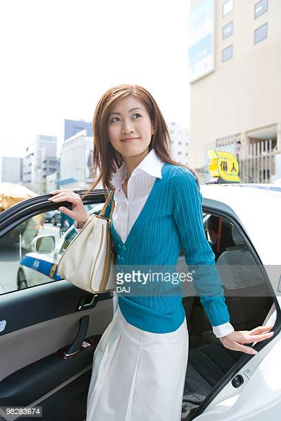 A Woman Getting out of Taxi