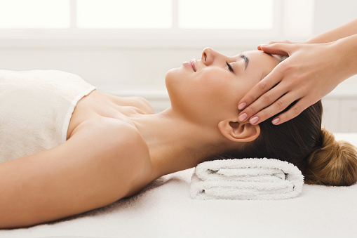 Woman getting professional facial massage at spa salon 936385994