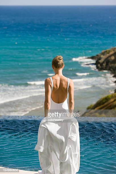 woman getting ready for a swim in an infinity pool