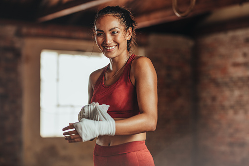 Woman getting ready for boxing practice 1047038486