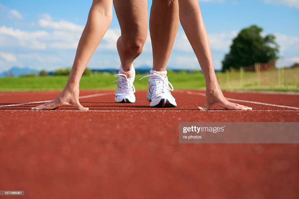 A woman getting ready to sprint on the track and field : Stock Photo