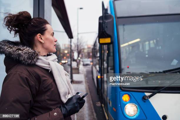 woman getting ready to step on bus cummuting in winter. - montreal stock pictures, royalty-free photos & images