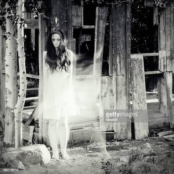 Woman ghost in front of an abandoned house