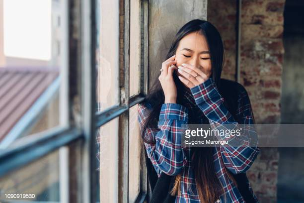 woman giggling on smartphone with hand over mouth - hands covering mouth stock pictures, royalty-free photos & images