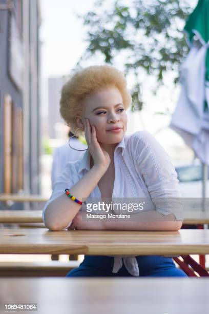 happy woman sitting outside in the city - thick black woman stock photos and pictures