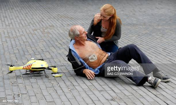 A woman gives a demonstration of an ambulance drone with built in defibrillator at the campus of the Delft Technical University in Delft on October...