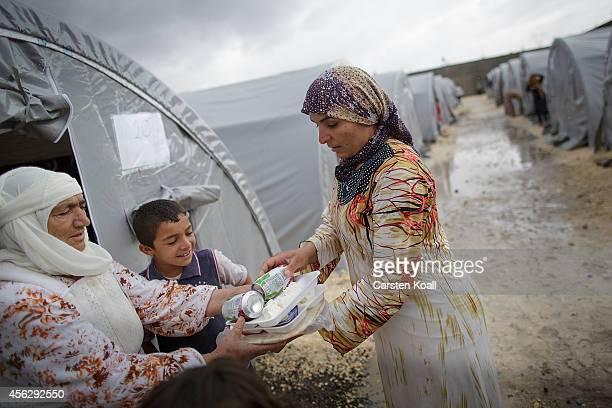 A woman gives a meal to a grandmother at their tent in a refugee camp after crossing from Syria into Turkey in Suruc September 28 2014 south of...