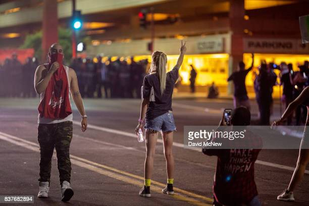 A woman gives a peace sign to police officers in riot gear after a rally by President Donald Trump at the Phoenix Convention Center on August 22 2017...