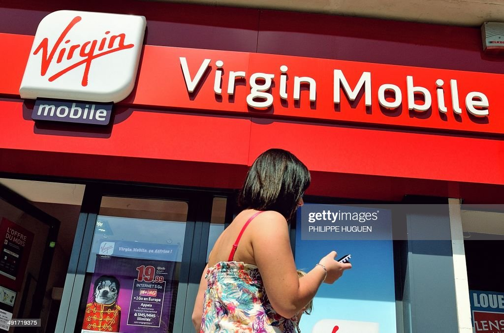 A woman gives a phone call as she walks by a shop of mobile phone