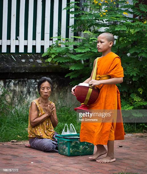 CONTENT] A woman gives alms to a passing young monk in the UNESCO World Heritage City of Luang Prabang Laos This is one of the most sacred Buddhist...