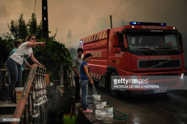 A woman gives directions to firefighters and other members of her family fill up buckets of water as a wildfire threatens the village of Capelo in...