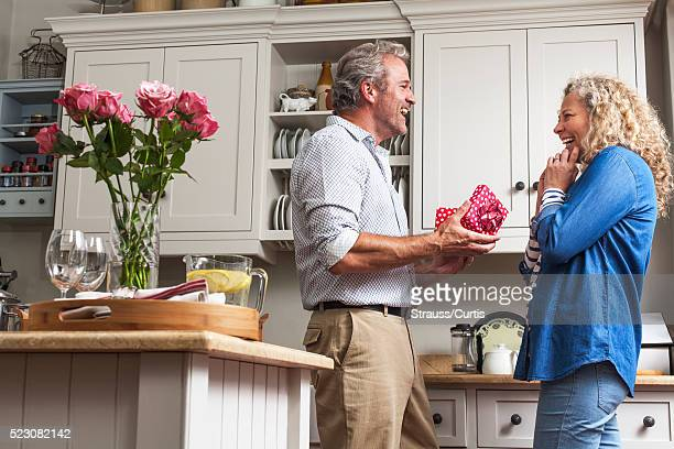 woman gives gift to man - anniversary stock pictures, royalty-free photos & images