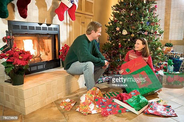 A woman gives her husband a big gift on Christmas morning.