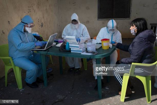 A woman gives her personal information to a team of health workers performing free antibody and COVID19 testing in the primarily Roma neighborhood of...