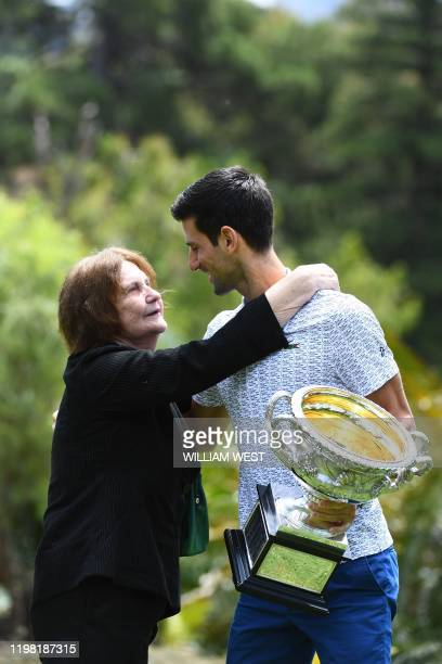A woman gives Serbia's Novak Djokovic a hug as he takes part in a photo shoot at the Royal Botanical Gardens in Melbourne on February 3 a day after...