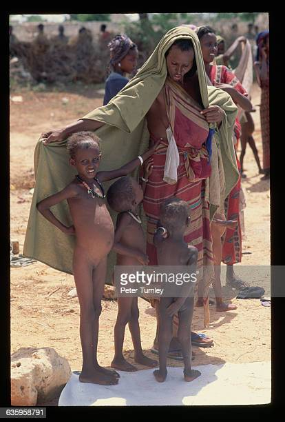 A woman gives three children shelter under her shawl at a relief center during the famine crisis In the 1980s warlord factions joined together to...