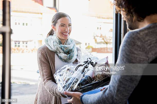 Woman giving a gift to her friend at front door, Munich, Bavaria, Germany