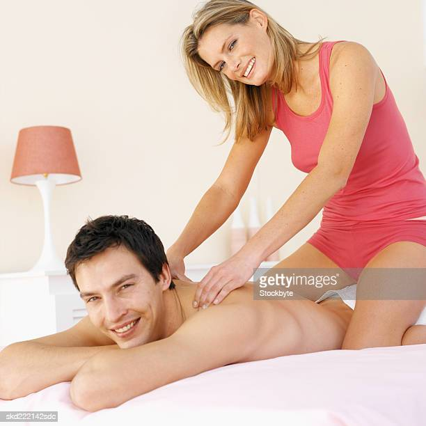 Woman giving a man a massage in bed