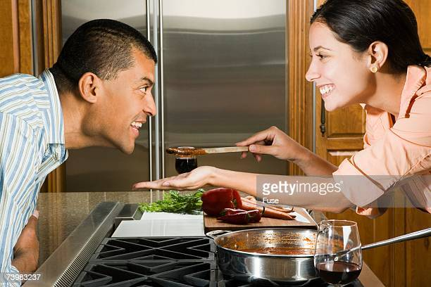 Woman giving a man a taste of sauce
