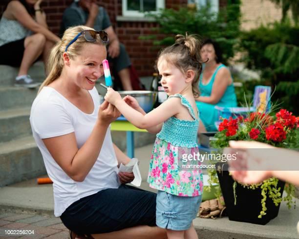 frau einem kleines mädchen auf familientreffen ein eis am stiel verleiht. - taufpatin stock-fotos und bilder