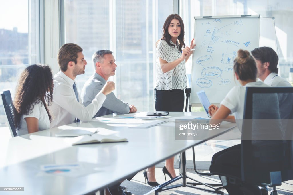 Woman giving a presentation to her team. : Stock Photo