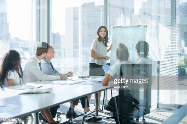 woman giving a presentation to her team. - corporate business stock pictures, royalty-free photos & images