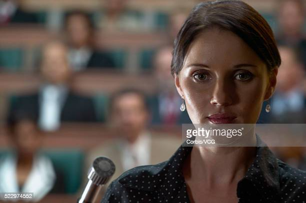 a woman giving a speech in front of an audience - witness stock pictures, royalty-free photos & images
