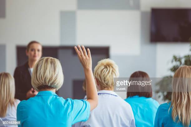 woman giving a speech on seminar for medical staff - debate stock photos and pictures