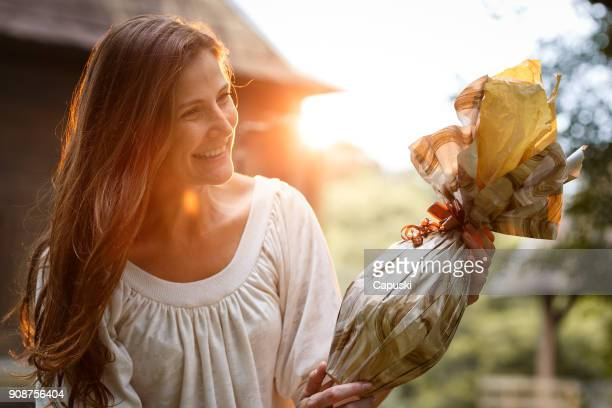 a woman giving an easter egg - easter stock pictures, royalty-free photos & images