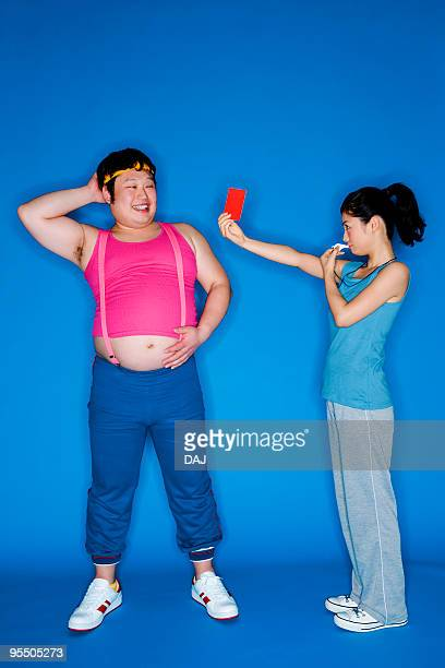 woman giving an overweight man a red card - carton rouge photos et images de collection