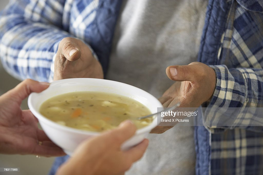 Woman giving bowl of soup to man : Stock Photo