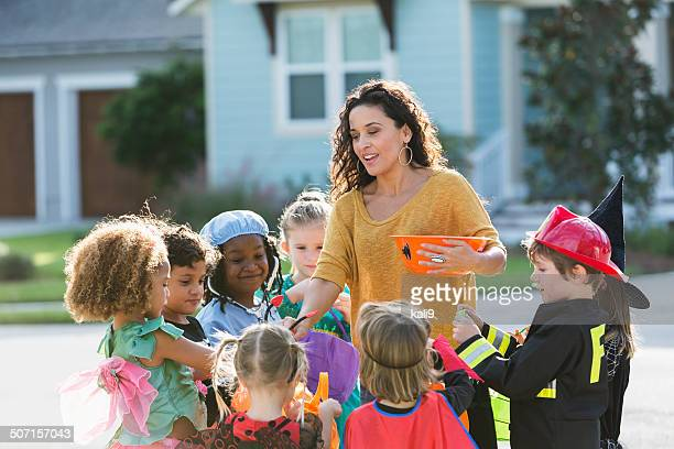 Woman giving candy to children trick or treating