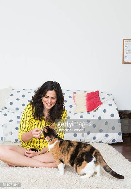 Woman giving cat a treat in living room