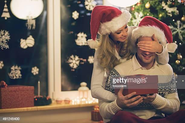 mujer dando regalo de navidad a un hombre - recibir fotografías e imágenes de stock