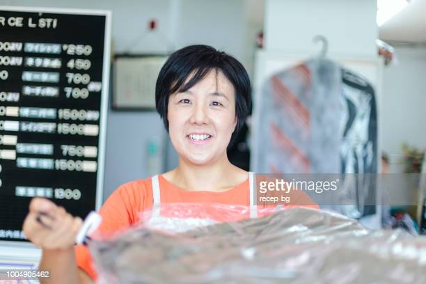 Woman giving clothes to customer in dry cleaning shop. Photo from the point of view of customer.