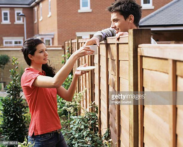 woman giving coffee to neighbour - hek stockfoto's en -beelden