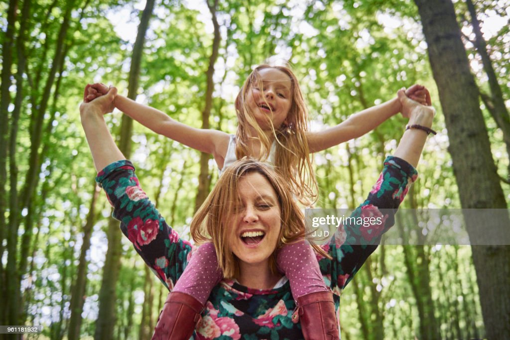 Woman giving daughter a shoulder ride in forest : Stock Photo