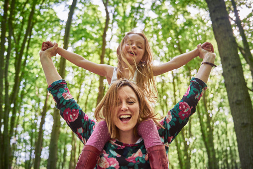 Woman giving daughter a shoulder ride in forest - gettyimageskorea