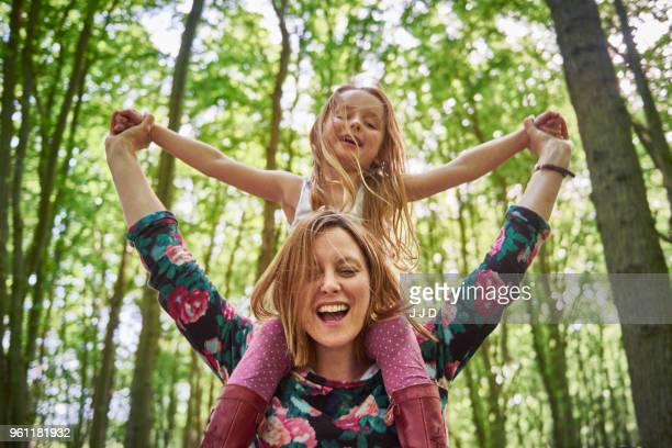 woman giving daughter a shoulder ride in forest - im freien stock-fotos und bilder