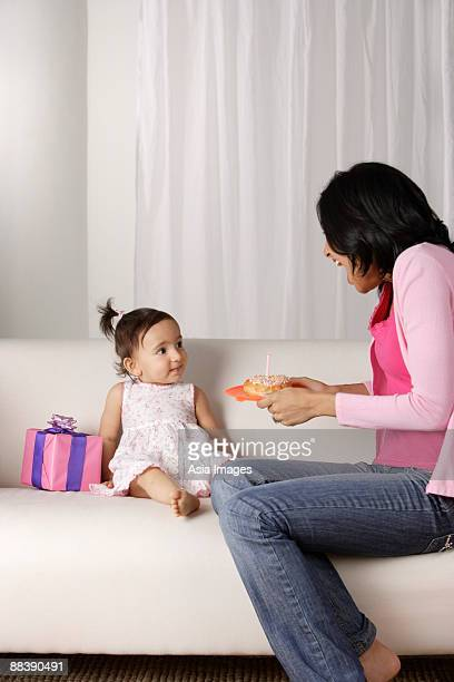 woman giving food to baby