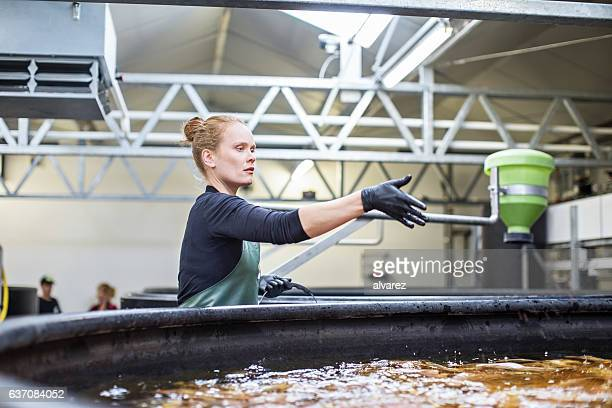 Woman giving food to fishes in tanks