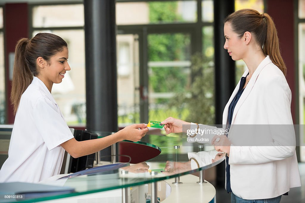 Woman giving french social security card to receptionist at hospital reception desk : Foto de stock