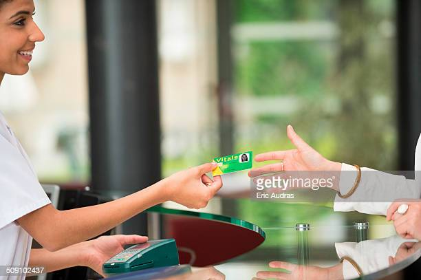 woman giving french social security card to receptionist at hospital reception desk - 手渡す ストックフォトと画像