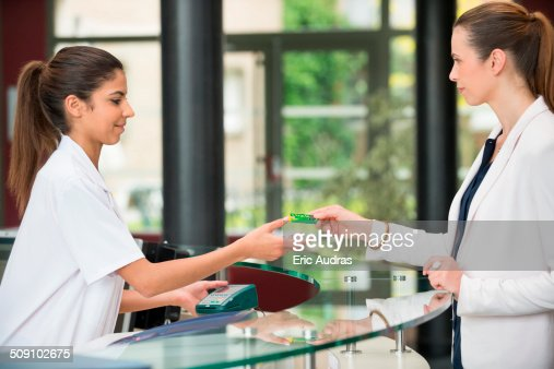 woman giving french social security card to receptionist at hospital reception desk stock photo getty images