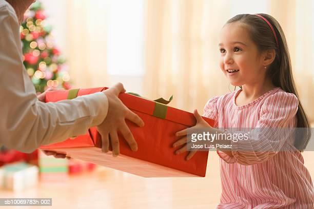 Woman giving gift to girl (4-5)