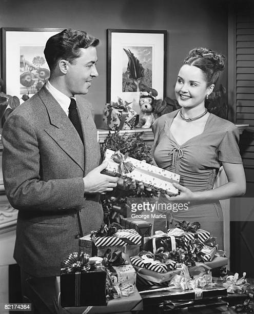 woman giving gift to man, (b&w) - christmas past and christmas present stock pictures, royalty-free photos & images