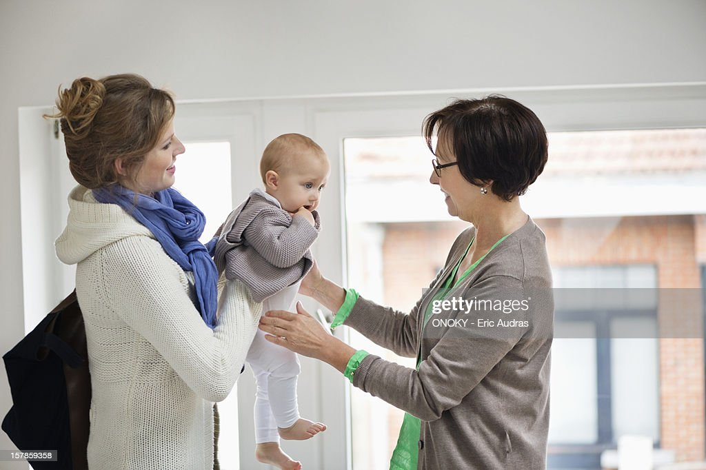 Woman giving her daughter to nanny : ストックフォト