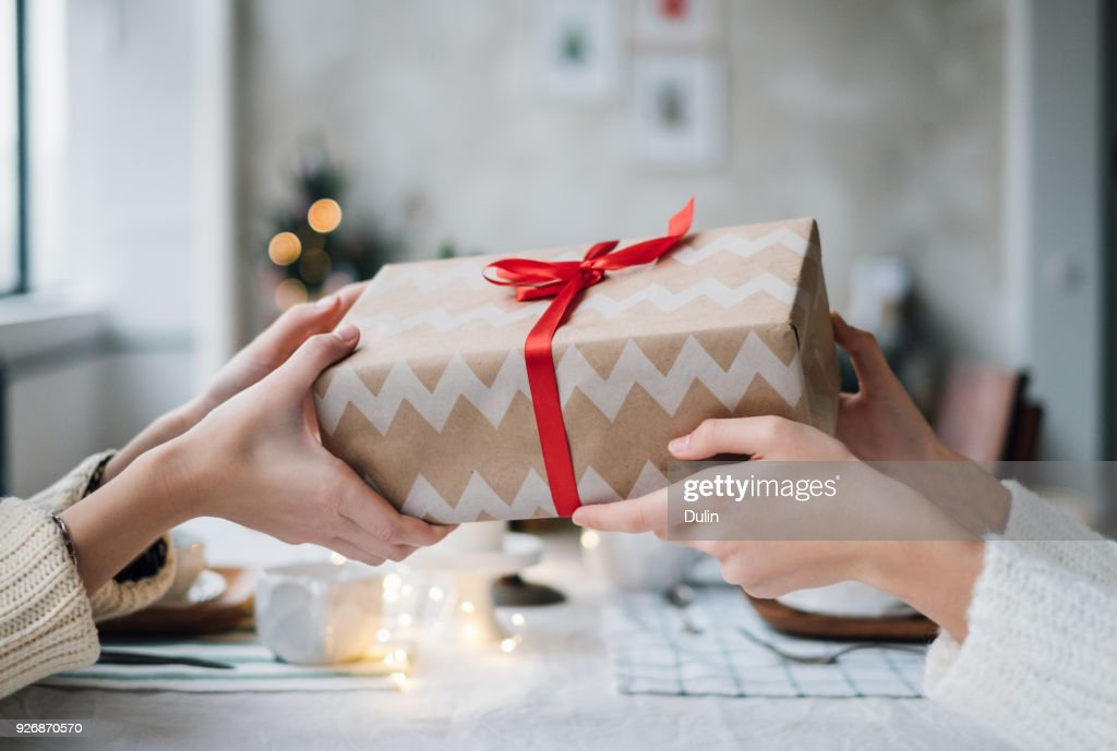 Woman giving her friend a wrapped Christmas gift : Stock Photo