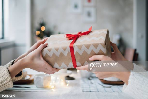 woman giving her friend a wrapped christmas gift - geben stock-fotos und bilder